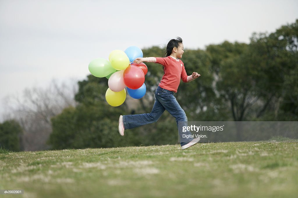 Girl Running with a Bunch of Balloons : Stock Photo