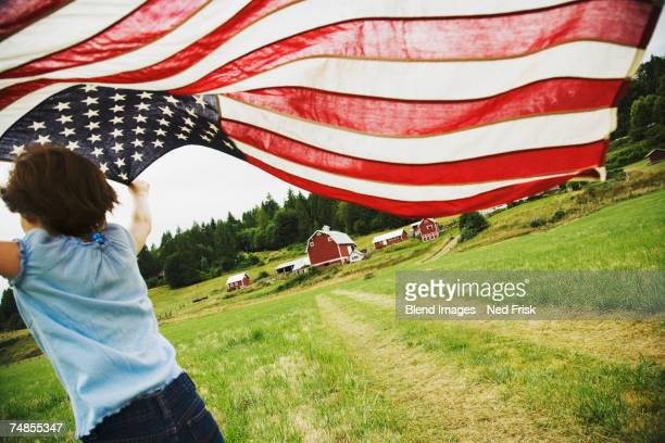 Girl running with American flag on farm