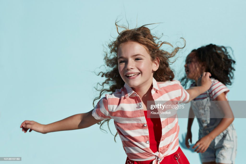 Girl running with arms out, on studio background : Stock Photo
