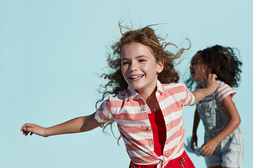 Girl running with arms out, on studio background - gettyimageskorea