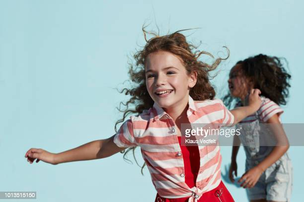 girl running with arms out, on studio background - vestido azul fotografías e imágenes de stock