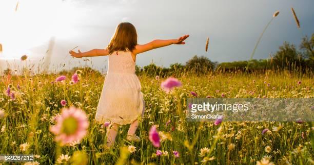 Mädchen mit ausgestreckten auf Feld laufen