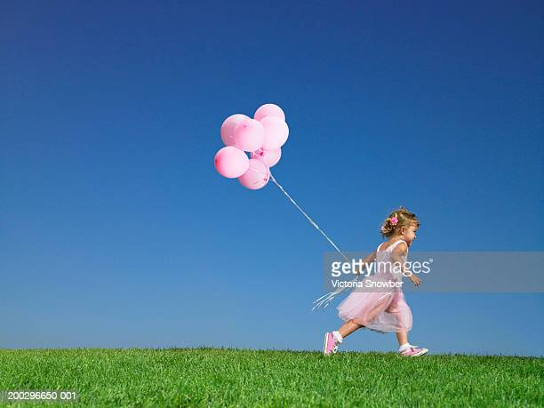 Girl (2-4) running with balloons in field