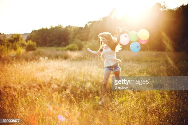 Girl running with balloons in sunny field