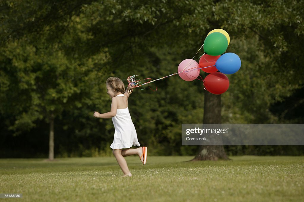Girl running with balloons outdoors : Stockfoto