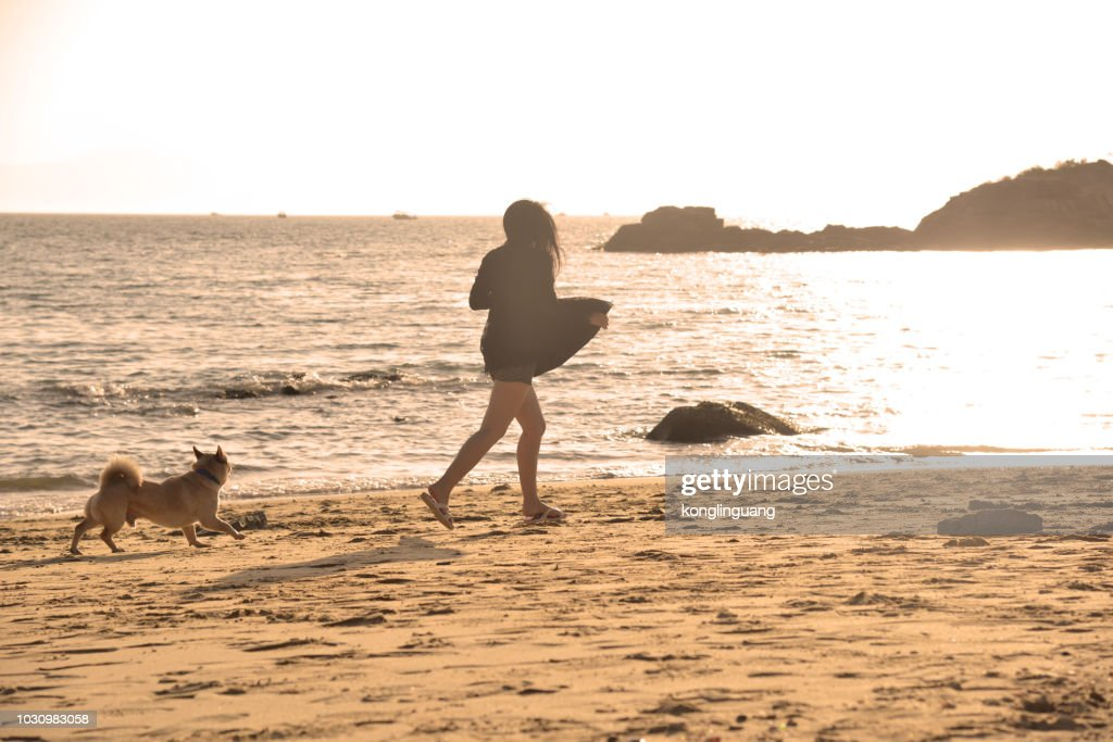 A girl running with her dog on the sea beach. : Stock Photo