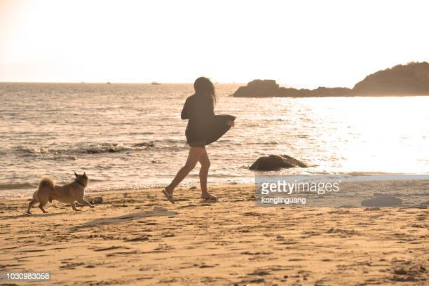 A girl running with her dog on the sea beach.