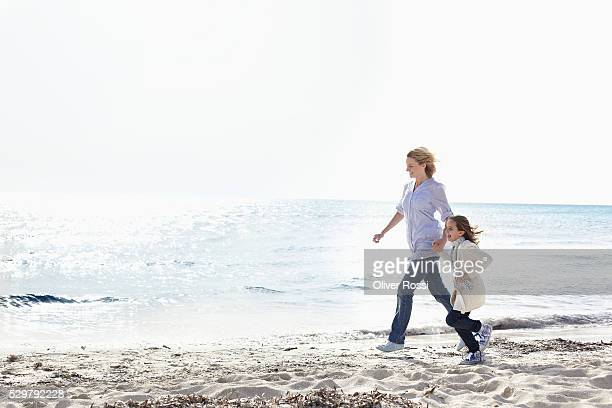 Girl (7-9) running with mother on beach