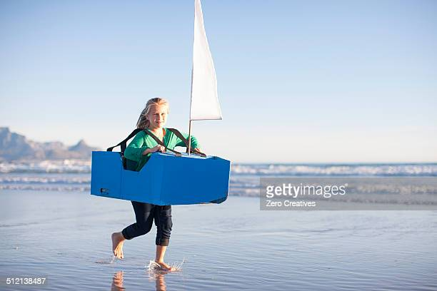 Girl running with toy boat along beach