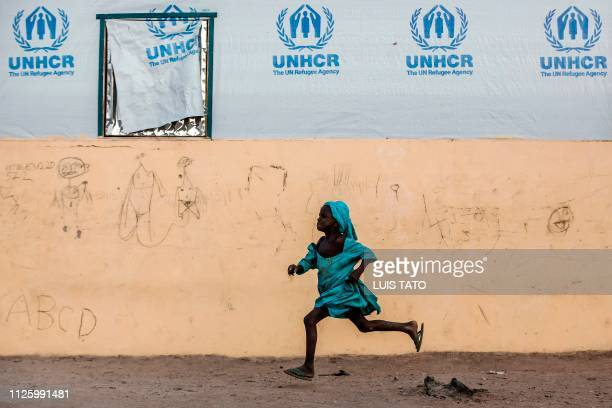 TOPSHOT A girl runs at Malkohi refugee camp in Jimeta Adamawa State Nigeria on February 19 four days ahead of the country's General elections set for...