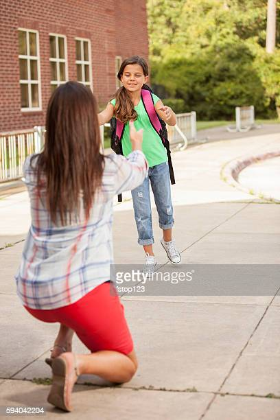 Girl runs back to mom on first day of school.