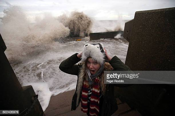 A girl runs from waves crashing over the promenade on December 24 2015 in Blackpool England The Met Office is warning of 80mph winds and torrential...