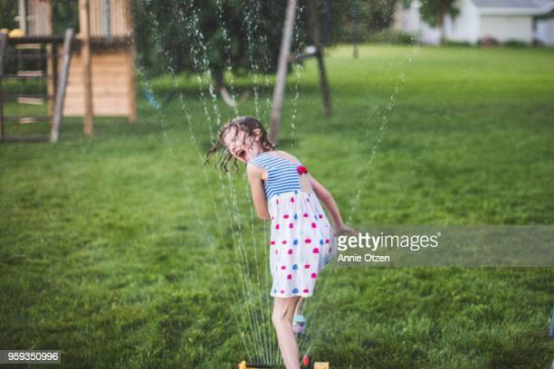 Girl runs headfirst through sprinkler