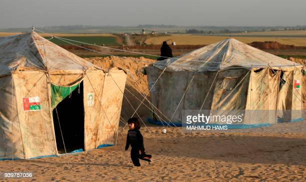 Girl runs next to tents pitched by Palestinians on the Gaza border with Israel , east of Jabalia, on March 29 ahead of a six-week protest camp. The...