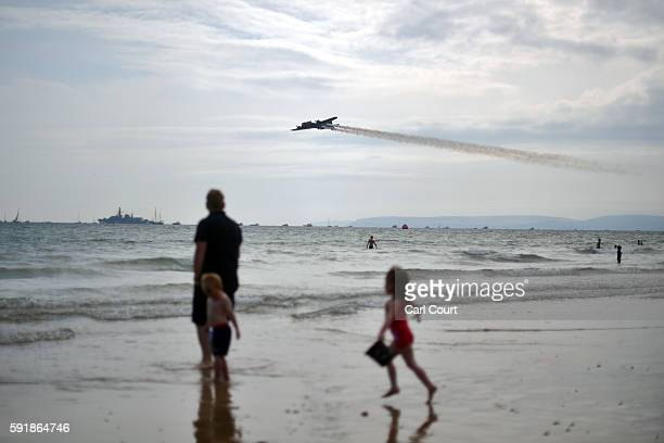 A girl runs on the beach as a Boeing B17 Flying Fortress flies past during the Bournemouth Air Festival on August 18 2016 in Bournemouth England The...
