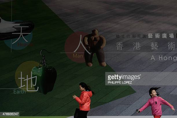 A girl runs past a large billboard promoting a thematic exhibition at the Museum of Art in Hong Kong on March 6 2014 The Hong Kong Museum of Art...