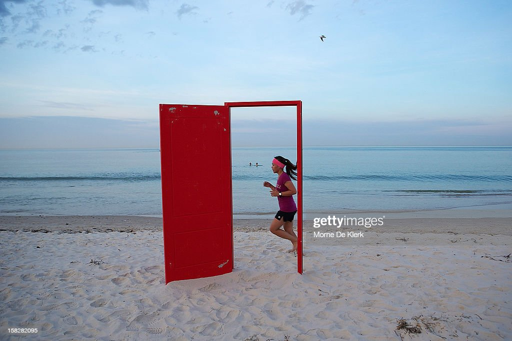 A girl runs past a red door to be used in an installation by surrealist artist, Andrew Baines at Henley Beach on December 13, 2012 in Adelaide, Australia. The installation was called 'Doorways To Potential'.