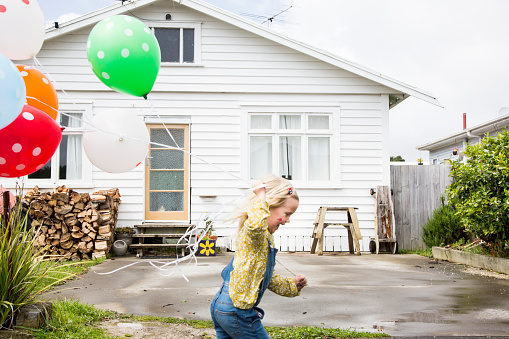 Girl runs past the front of a bungalow holding colourful balloons - gettyimageskorea