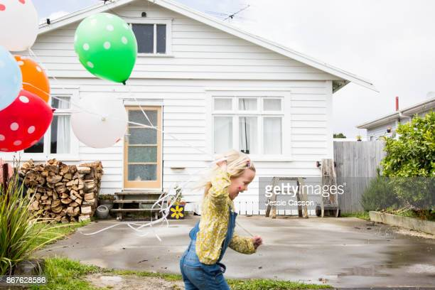 Girl runs past the front of a bungalow holding colourful balloons