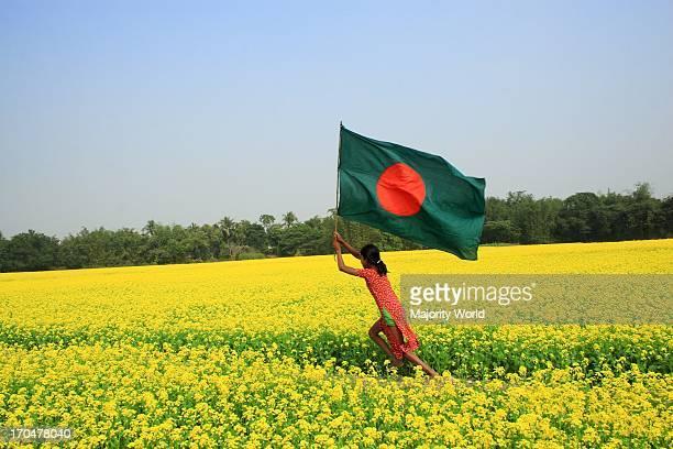 A girl runs through a mustard field hoisting the National flag Manikganj Bangladesh February 5 2008
