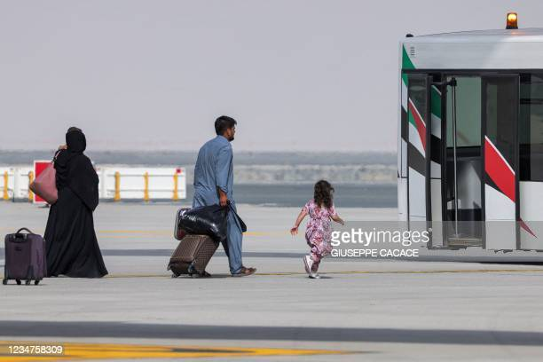 Girl runs towards an airport shuttle bus as people disembark off a Royal Air Force military transport aircraft carrying evacuees from Afghanistan and...