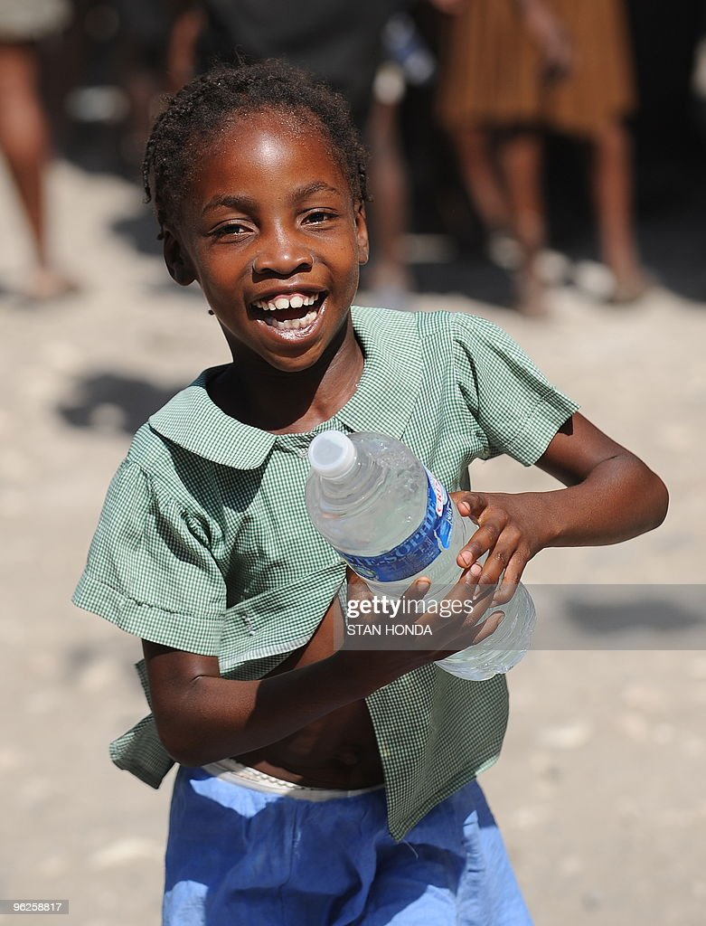 A girl runs with a bottle of water distributed by a Sri Lankan United Nations unit January 23, 2010 in Leogane, Haiti. The Sri Lankans handed out food and water donated by the US for earthquake relief. AFP PHOTO/Stan Honda