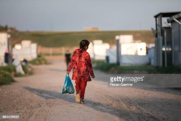 A girl runs with a plastic bag filled with food through the refugee camp 'Hasansham U3' near Hasansham on April 20 2017 in Hasansham Iraq