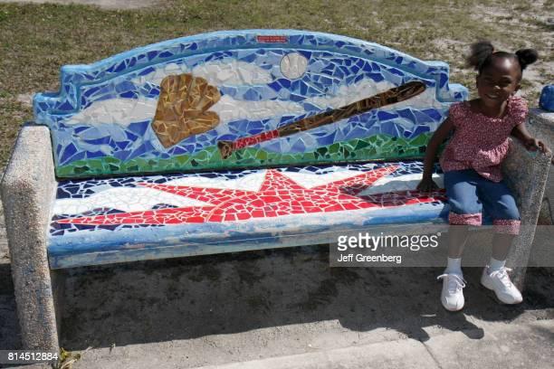 A girl sat on a baseball theme mosaic park bench at Fort Pierce