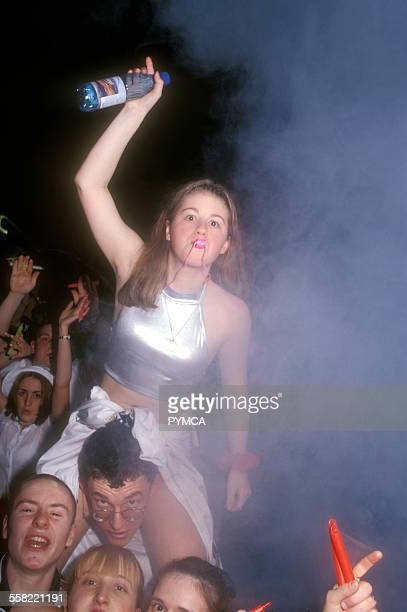 A girl sat on a guys shoulders raving blowing a whistle in the crowd Clubbing Edinburgh UK 2000s