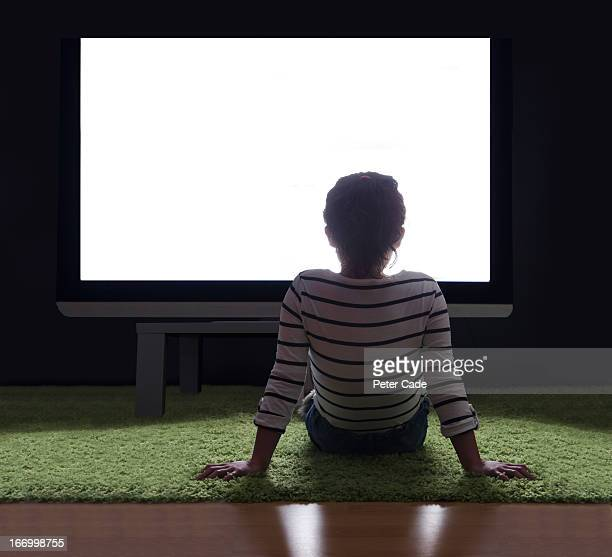 Girl sat on floor in front of large white screen