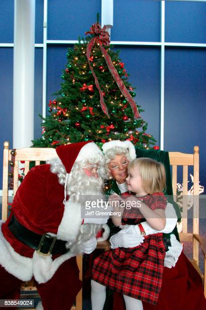 A girl sat on Mrs Claus lap talking to Santa for Breakfast with Santa at Virginia Air Space Museum