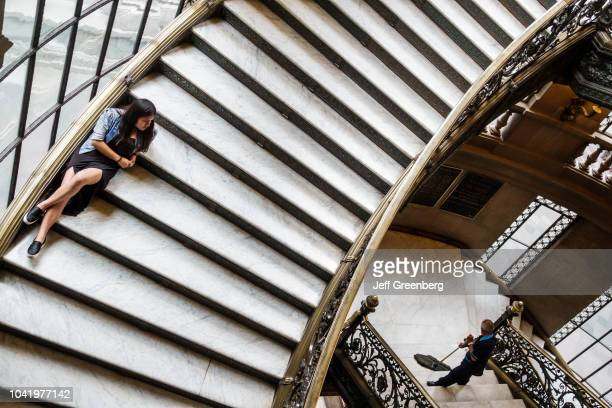 A girl sat on the central stairway inside the National Museum of Art