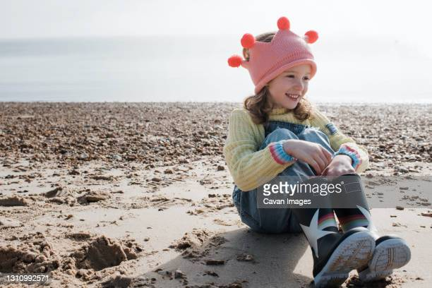 girl sat smiling on the beach wearing a crown on a sunny day in the uk - queen royal person stock pictures, royalty-free photos & images