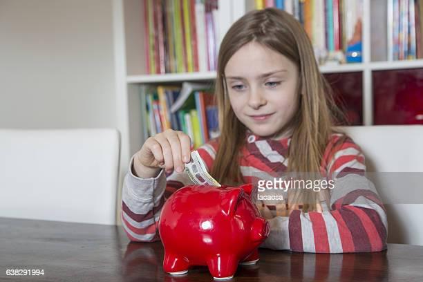 Girl saving money in red piggy bank