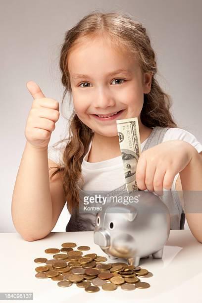 Girl saving money with a piggybank