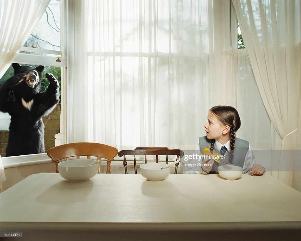 Girl scared by bear at the window : Stock Photo