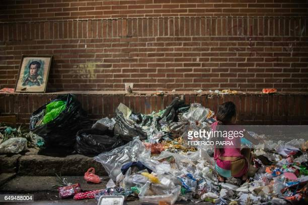 A girl scavanges for food in the streets of Caracas on February 22 2017 Venezuelan President Nicolas Maduro is resisting opposition efforts to hold a...