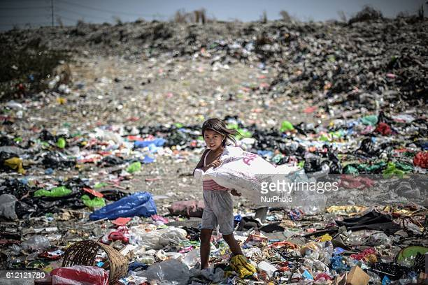A girl scavenges for recyclable materials at a garbage dumpsite during Earth Day in Las Pinas south of Manila Philippines April 22 2014 The world...