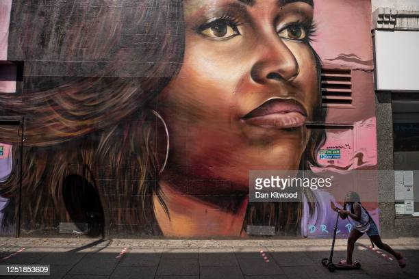 A girl scoots past a mural of Michelle Obama in Brixton on June 24 2020 in London England Yesterday the Prime Minister Boris Johnson announced the...