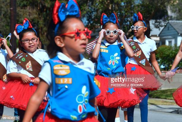 Girl Scout adjusts her Star shaped sunglasses during a Fourth of July parade in San Gabriel, California on July 4, 2018 as cities and towns across...