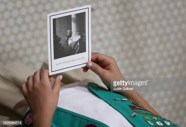 Girl Scout holds a picture of the late Sen John McCain as his body lies in state at the Arizona State Capitol on August 29 2018 in Phoenix Arizona...