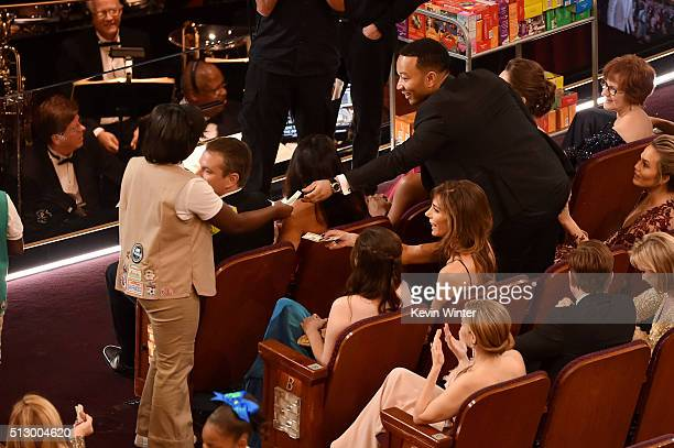 Girl Scouts sell cookies to audience members including musician John Legend during the 88th Annual Academy Awards at the Dolby Theatre on February 28...