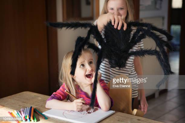 Girl screaming at a large toy spider
