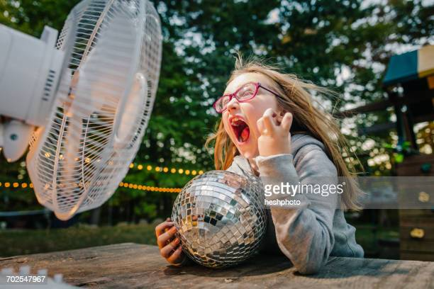 girl screaming in front of windy electric fan at garden table - heshphoto stock pictures, royalty-free photos & images