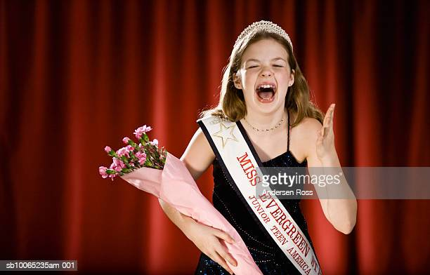 Girl (11-13) screaming on stage with bouquet of flowers in beauty pageant