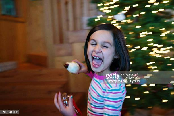 Girl Screaming While Decorating Christmas Tree