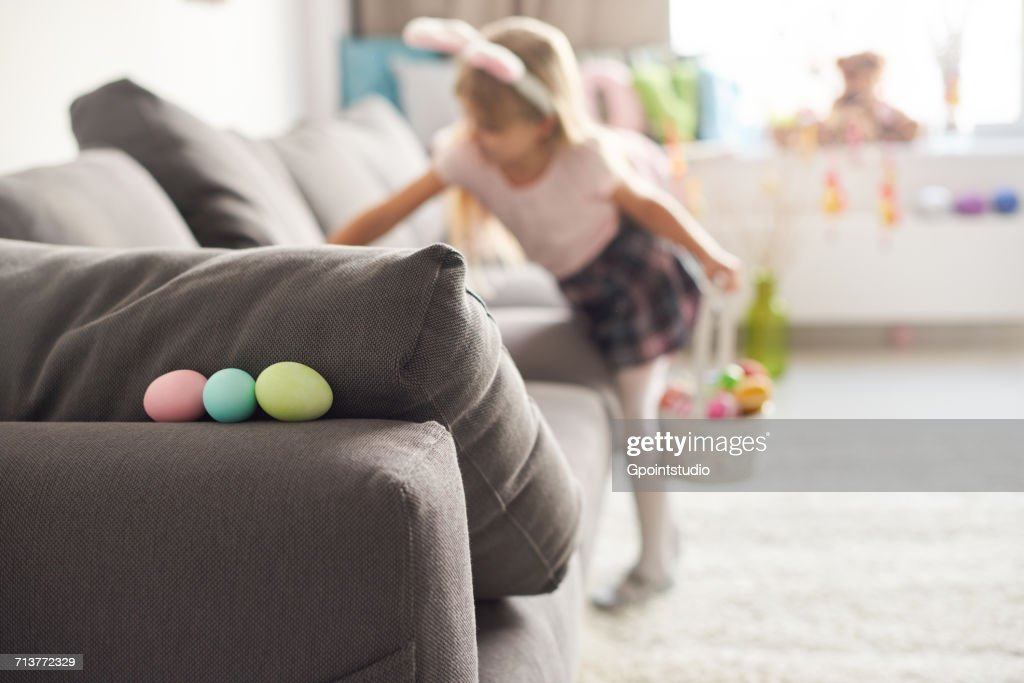 Girl searching for easter eggs on sofa : Stock Photo