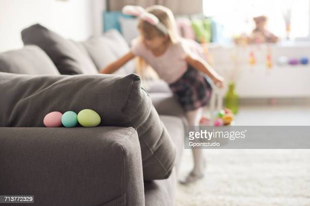 girl searching for easter eggs on sofa - chasse aux oeufs de paques photos et images de collection