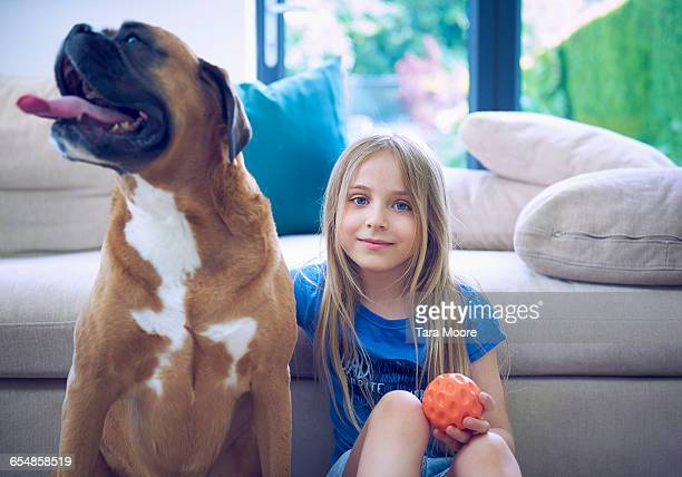 Girl seated on floor against sofa with big dog