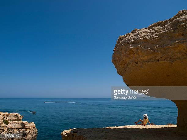 Girl seating under rock looking at the sea